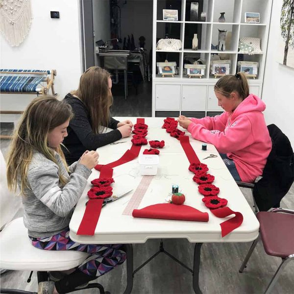 Threadheads students assembling Remembrance Day poppy sashes